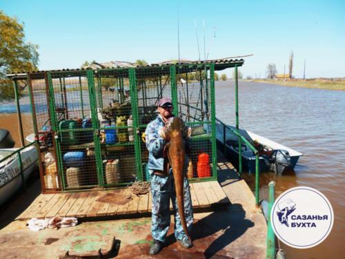 Рыбак с уловом трофейного сома